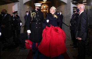 WASHINGTON, DC - JANUARY 20: Lady Gaga is escorted by U.S. Marine escort Capt. Evan Campbell to sing the National Anthem at the inauguration of U.S. President-elect Joe Biden on the West Front of the U.S. Capitol on January 20, 2021 in Washington, DC.  During today's inauguration ceremony Joe Biden becomes the 46th president of the United States. (Photo by Win McNamee/Getty Images)