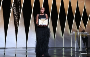 """French director Julia Ducournau poses on stage with her trophy after she won the Palme d'Or for her film """"Titane"""" during the closing ceremony of the 74th edition of the Cannes Film Festival in Cannes, southern France, on July 17, 2021. (Photo by Valery HACHE / AFP) (Photo by VALERY HACHE/AFP via Getty Images)"""